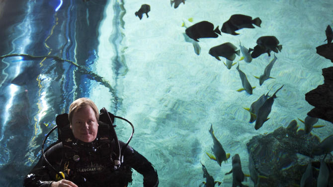 "In this photo taken on Saturday, July 28, 2012, American journalist and diving instructor Steven Schwankert in diving suit swims inside the Blue Zoo aquarium in Beijing. A lifelong scuba diving obsession led Schwankert to the tale of the HMS Poseidon and the startling discovery that the British submarine, which sank off the northeastern coast of China in the 1930s, had been raised by the Chinese in 1972. That revelation lies at the heart of Schwankert's upcoming book, ""The Real Poseidon Adventure: China's Secret Salvage of Britain's Lost Submarine"" and an accompanying documentary film chronicling his search for answers about what became of the sunken vessel. (AP Photo/Andy Wong)"