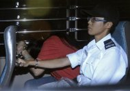 Catherine Au Yuk-shan (L), 41, a public hospital assistant, is escorted by a Hong Kong Correctional Services Department officer inside a van leaving Wanchai District Court for jail, in Hong Kong September 18, 2013. REUTERS/Stringer