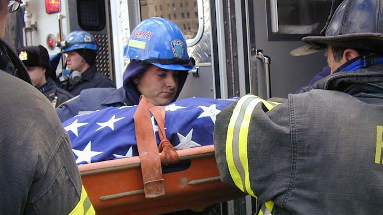 "In this undated photo provided by Stony Brook University, New York City police and firefighters remove the body of a victim recovered at the World Trade Center site in New York in the aftermath of the Sept. 11, 2011 attacks on the trade center. The WTC Medical Monitoring and Treatment Program at Stony Brook has cared for 6,000 first responders, many of whom have been videotaped recounting their experiences. A documentary featuring their recollections, with a companion book titled ""We're Not Leaving,"" are being released to mark the 10th anniversary.  (AP Photo/Stony Brook University, Steve Spak)"