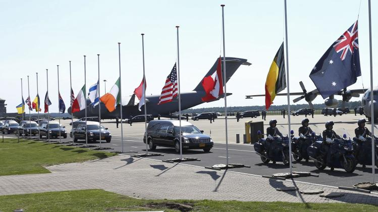 The convoy of hearses with the remains of the victims of Malaysia Airlines MH17 downed over rebel-held territory in eastern Ukraine, drives past international flags as it leaves Eindhoven airport to a military base in Hilversum
