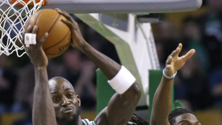 Boston Celtics power forward Kevin Garnett (5) brings down a rebound against Denver Nuggets small forward Kenneth Faried (35) during the first half of an NBA basketball game in Boston, Sunday, Feb. 10, 2013. (AP Photo/Elise Amendola)