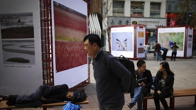 A man walks past an elderly man sleeps on a bench at the Wangfujing shopping district in Beijing, China Tuesday, Oct. 21, 2014. China's economic growth waned to a five-year low of 7.3 percent last quarter, raising concerns of a spillover effect on the global economy but falling roughly in line with Chinese leaders' plans for a controlled slowdown. (AP Photo/Andy Wong)