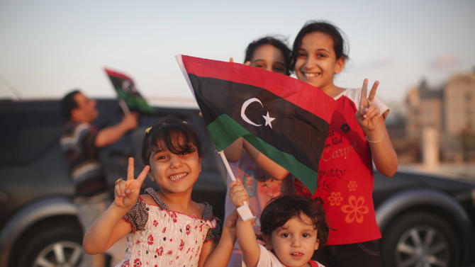 Bashir Khamis, 2, front, poses for a photo together with his sisters at seaside of the rebel-held town of Benghazi, Libya, Monday, Aug. 22, 2011. World leaders said Monday the end is near for Moammar Gadhafi's regime and began looking at Libya's future without the man who has held power there for 42 years. (AP Photo/Alexandre Meneghini)