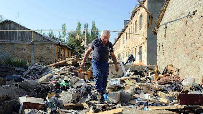 A man walks through rubble as he examines his destroyed house after shelling between Ukrainian forces and pro-Russian separatists on August 10, 2015 in Golmovsky village