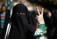 A Palestinian woman raises her hand written with the Arabic words &quot;our prisoners are our dignity&quot; as she takes part in a protest against the death of a Palestinian detainee in an Israeli jail, in Gaza City February 24, 2013. REUTERS/Suhaib Salem