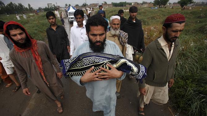 A man carries the body of his son for burial after he was killed when a rooftop of his house collapsed due to heavy rain in the outskirts of Peshawar