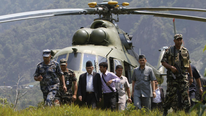 Nepal's Prime Minister Baburam Bhattarai, third left, arrives to inspect the site of a flash flood at Kharapani village of Kaski district, about 200 kilometers (125 miles) west of Katmandu, Nepal, Sunday, May 6, 2012. Flash floods from the Seti river in western Nepal swept away dozens of people along with their cattle and houses, officials said. Bodies have been recovered, a police official said.(AP Photo/Niranjan Shrestha)