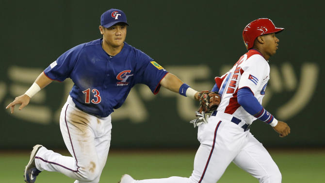 Cuba's shortstop Erisbel Arruebarruena, right,  is tagged out by Taiwan's third baseman Chen Yung-chi in a pickle in the third inning of their World Baseball Classic second round game at Tokyo Dome in Tokyo, Saturday, March 9, 2013. (AP Photo/Koji Sasahara)