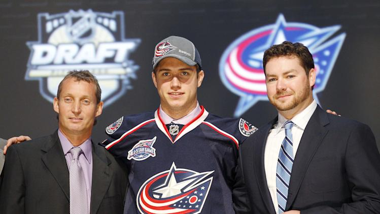 Ryan Murray , center, a defenseman, stands with officials from the Columbus Blue Jackets after being chosen second overall in the first round of the NHL hockey draft on Friday, June 22, 2012, in Pittsburgh. (AP Photo/Keith Srakocic)
