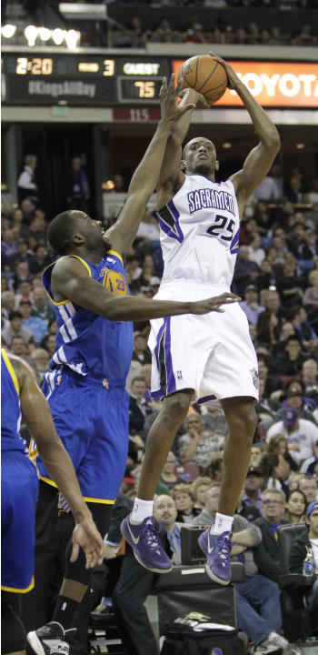 Sacramento Kings forward Travis Outlaw, right, shoots over Golden State Warriors forward Draymond Green during the third quarter of an NBA basketball game in Sacramento, Calif., Wednesday, Feb. 19, 20
