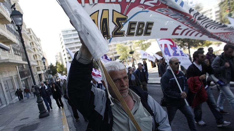 A protester holds a banner during a protest from the confederation of Professionals, Craftsmen and Merchants against a new austerity bill that will be discussed in Parliament, in Athens on Sunday, March 30 2014. The measures demanded by bailout lenders will be voted on late Sunday, and would liberalize several retail sectors. They include plans to grant supermarkets permission to set up in-store pharmacies, scrap price limits on books and allow a longer shelf-life for milk. (AP Photo/Kostas Tsironis)