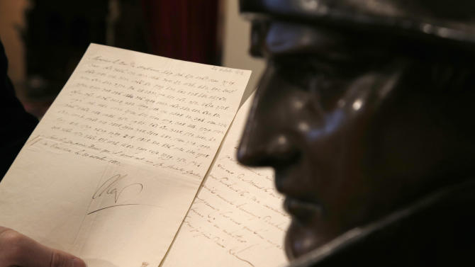 """In this photo taken Wednesday, Nov. 28, 2012, a letter dictated and signed by Napoleon in secret code that declares his intentions """"to blow up the Kremlin"""" during his ill-fated Russian campaign is displayed for the media in Fontainebleau, outside Paris. The rare letter, written in unusually emotive language, sees Napoleon complain of harsh conditions and the shortcomings of his grand army. The letter goes on auction Sunday, Dec. 2, 2012. (AP Photo/Christophe Ena)"""