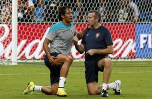 Portugal's defender Bruno Alves chats with his physician during a training session in Manaus