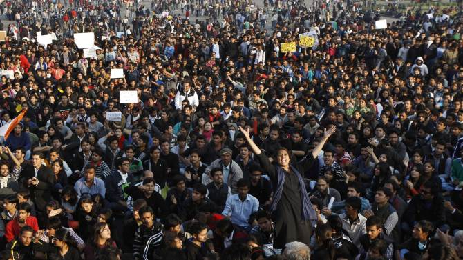 FILE - In this Dec. 22, 2012 file photo, people crowd outside the Presidential Palace as they protest against a brutal gang rape of a 23-year-old student, in New Delhi, India. The sadness enveloped her father as he talked of his daughter, who died at a Singapore hospital on Dec. 29, after she was gang-raped in a moving bus in New Delhi in December, a case that galvanized public anger in India over sexual attacks and the inability of authorities to stop them. (AP Photo/Tsering Topgyal, File)