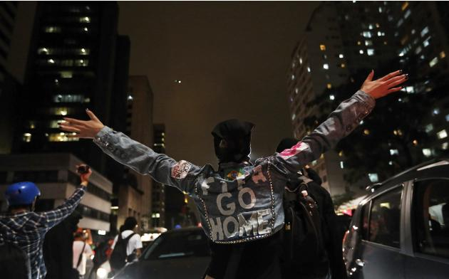 A demonstrator spreads her arms open during a protest against the 2014 World Cup, in Sao Paulo
