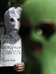 Masked demonstrators attend a demonstration in support of the Russian punk group Pussy Riot, whose members face prison for a stunt against President Vladimir Putin, outside Russia's embassy in Berlin, Friday, Aug. 17, 2012. The three female band members have been in jail for more than five months because of an anti-Putin prank in Moscow's main cathedral. A judge is due to rule on their case Friday. The poster reads: Pussy Riot is the last conscience of Russia. (AP Photo/Markus Schreiber)