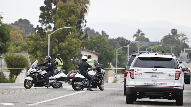 Chula Vista, Calif. police block E Street during a standoff with man allegedly possessing a AK 47 rifle and holding hostages Thursday, May 28, 2015, in Chula Vista, Calif. Authorities are negotiating with a man who is believed to be holed up in his apartment with two children and a woman after a shooting outside the housing complex. (AP Photo/Lenny Ignelzi)