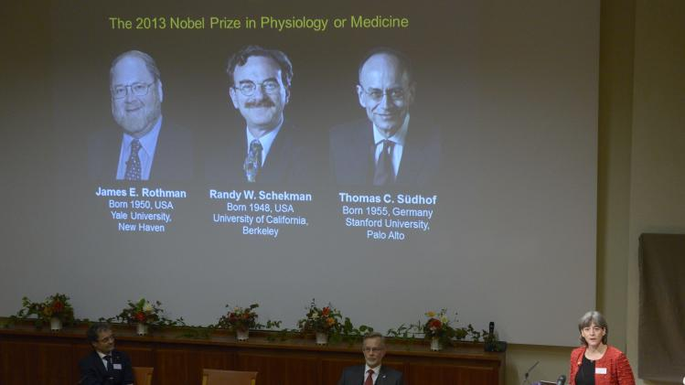 Karolinska Institute's Chairman of the Nobel committee for physiology or medicine Juleen Zierath talks, as images of James Rothman and Randy Schekman, of the United States, and German-born researcher Thomas Sudhof are projected on a screen, in Stockholm, Sweden, Monday, Oct. 7, 2013, as they are announced as the winners of the 2013 Nobel Prize in medicine. Rothman, Schekman and Sudhof won the 2013 Nobel Prize in medicine on Monday for discoveries on how proteins and other materials are transported within cells. (AP Photo/ TT News Agency Janerik Henriksson) SWEDEN OUT