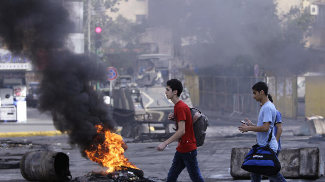 Lebanese students pass  a burning tire laid by Sunni protesters, angry at the killing of Brig. Gen. Wissam al-Hassan, to block a road in Beirut, Lebanon, Saturday, Oct. 20, 2012. A car bomb ripped through Beirut on Friday, killing a top security official and several others, shearing the balconies off apartment buildings and sending bloodied residents staggering into the streets in the most serious blast the Lebanese capital has seen in four years. Dozens of people were wounded in the attack, which the state-run news agency said targeted the convoy of Brig. Gen. Wissam al-Hassan, a top security official in Lebanon. (AP Photo/Hussein Malla)