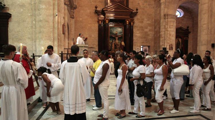 Members of the Ladies in White dissident group line up to kiss a statue of Jesus Christ during a mass as part of Good Friday celebrations in Havana