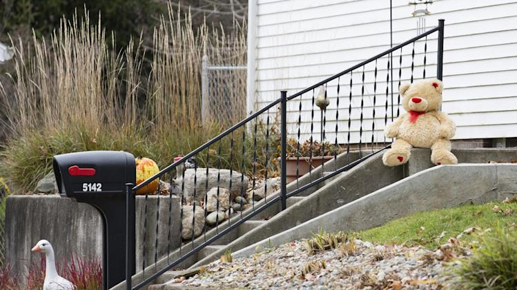 A lone teddy bear sits on the steps of the home Tuesday Nov. 13, 2012 in Toledo, Ohio.   Three children, their uncle, and their grandmother were found dead inside a garage at the house Monday in what appears to be a murder-suicide amid a custody dispute. (AP Photo/Rick Osentoski)