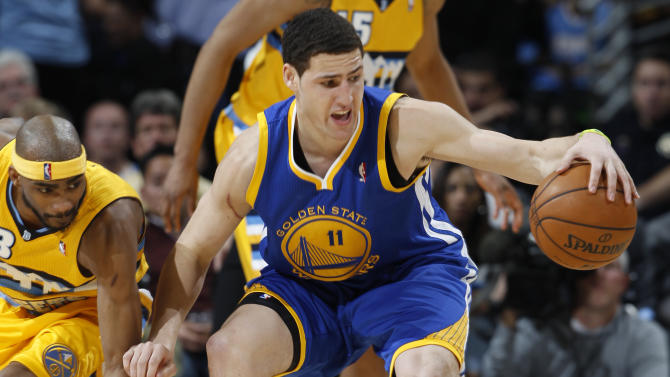 Golden State Warriors guard Klay Thompson, right, reahes out to pull in a loose ball as Denver Nuggets forward Corey Brewer covers in the fourth quarter of the Warriors' 131-117 victory in Game 2 of the teams' NBA first-round playoff series in Denver on Tuesday, April 23, 2013. (AP Photo/David Zalubowski)