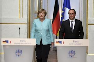 French President Hollande and German Chancellor Merkel arrive at a joint statement at the Elysee Palace in Paris