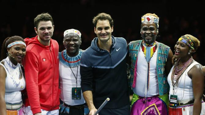 "Switzerland's Federer poses with compatriot Wawrinka and artists after ""The match for Africa 2"" charity tennis match in Zurich"