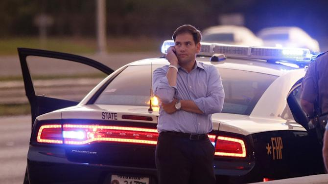 Sen. Marco Rubio, R-Fla., who is traveling with Republican presidential candidate and former Massachusetts Gov. Mitt Romney, uses a phone as he stands alongside Interstate 4 in Lakewood Crest, Fla., Saturday, Oct. 27, 2012 after the motorcade was stopped. The 12-year-old daughter of Sen. Rubio had been airlifted to a hospital after a Saturday motor vehicle accident. A Rubio spokesman reports that the girl is in stable condition. (AP Photo/Charles Dharapak)