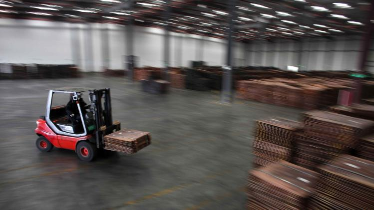 File picture shows a worker loading copper cathodes into a warehouse near Yangshan Deep Water Port, south of Shanghai