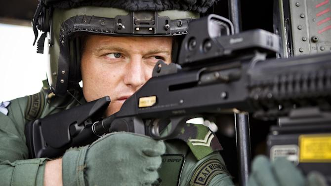 "In this photo released by the British MOD, a sniper with Royal Air Force Regiment Sniper, sights through his scope from inside an RAF Puma helicopter at RAF Northolt ahead of carrying out air security duties for Op Olympic, in London, Friday July 13, 2012.  Royal Air Force Puma Helicopters and Typhoon fighter jets along with Royal Navy Sea King helicopters are arriving at RAF Northolt ahead of the London 2012 Olympic Games to carry out air security. Aircraft that fail to comply with procedures within a restricted airspace zone around Olympic venues could be subject to ""lethal force"" from the military, it is revealed Friday. (AP Photo / NEIL CHAPMAN, Ministry of Defence)"