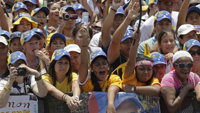 Supporters of opposition presidential candidate Henrique Capriles cheer as they wait for the arrival of Capriles for a campaign rally in Caracas, Venezuela, Sunday, April 7, 2013. Capriles is running against ruling party candidate Nicolas Maduro in next weekend's presidential election.(AP Photo/Ariana Cubillos)
