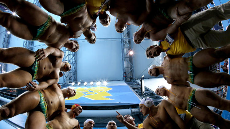 In this photo taken with a fisheye lens, Australia coach John Fox, pointing finger at bottom center right, talks to his players before a men's quarterfinal water polo match against Serbia at the 2012 Summer Olympics, Wednesday, Aug. 8, 2012, in London. (AP Photo/Julio Cortez)