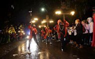 Flambeaus parade down St. Charles Avenue during the Krewe of Orpheus Mardi Gras parade in New Orleans, Monday, Feb. 11, 2013. (AP Photo/Gerald Herbert)