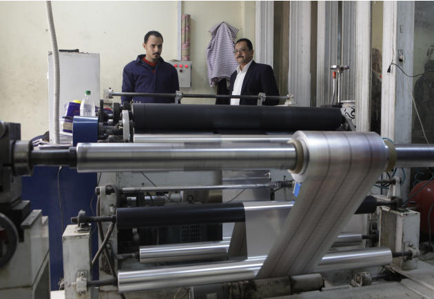 In this Monday, March 3, 2014 photo, Adel Abd ElSadk, left, owner of the pharmaceutical packaging company Trustpack, talks with an employee manning one of the machines at his factory which has been fi