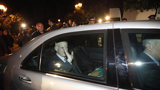 Greece's Prime Minister George Papandreou waves to journalists while exiting the Presidential Palace after a meeting with Greek President Karolos Papoulias and opposition leader Antonis Samaras, in Athens Sunday, Nov. 6 2011. Greece's embattled prime minister and the head of the main opposition party reached an initial agreement to form an interim government that will ensure the country's new European debt deal and then lead Greece to early elections, the president's office said. (AP Photo/Kostas Tsironis)