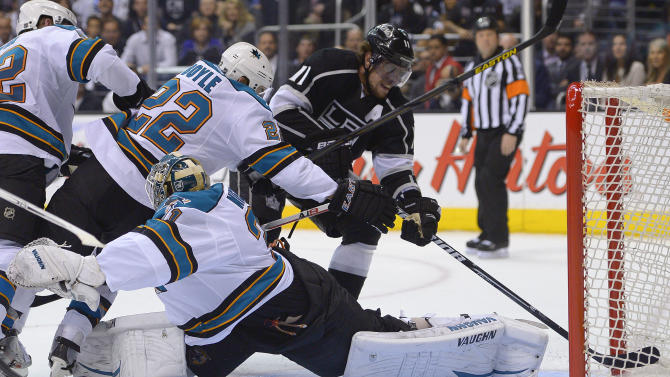 Los Angeles Kings center Anze Kopitar (11) pushes the puck across the goal line to score against San Jose Sharks goalie Antti Niemi (31) and defenseman Dan Boyle (22) in the second period during Game 5 of the Western Conference semifinals in the NHL hockey Stanley Cup playoffs, Thursday, May 23, 2013, in Los Angeles. (AP Photo/Mark J. Terrill)