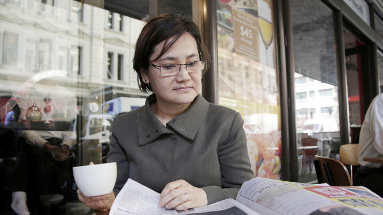 """Agnes Lee, 52, an IT consultant, reads a paper while having a coffee in Sydney, Thursday, Sept. 5, 2013. The ruling Labor Party's probable collapse in Australia's next election is largely the consequence of its qualified success in the last one three years ago. To form the coalition she needed to stay in power, then-Prime Minister Julia Gillard reneged on a promise and agreed to place a carbon tax on major polluters. """"The Labor government is all about themselves - the individual - rather than the whole party,"""" said Lee who plans to vote for the conservative coalition on Saturday. (AP Photo/Rick Rycroft)"""