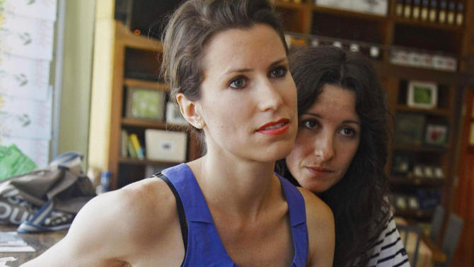 In this July 19, 2011 photo, Tiffany Peckosh, 31, left, and Meredith Soffrin, 30, listen during an interview in New York. Peckosh and Soffrin plan to marry Sunday, July 24, under New York's new gay marriage law. (AP Photo/Bebeto Matthews)