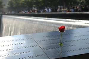 A single red rose is placed in the wall at the 9/11 Memorial in New York