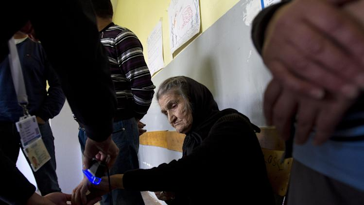Election official checks a old Serb woman for electoral stain before she is allowed to vote at a polling station in Kosovo capital Pristina on Sunday, Nov 3, 2013. People in Kosovo are voting in a local election that will test the country's fragile relations with Serbia as both seek to move closer to the European Union. Serb participation in Kosovo's political life is a key element of an EU-brokered deal that seeks to settle the dispute over Kosovo and unlock EU funds. (AP Photo/Visar Kryeziu)
