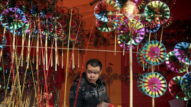 A vendor selling toys and decoration waits for customers inside his booth as the Chinese Lunar New Year which welcomes the Year of the Monkey is celebrated at Daguanyuan park, in Beijing