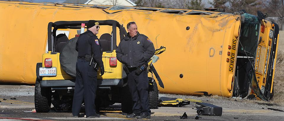 Emergency personnel stand at the scene where a school bus carrying around two dozen elementary school children overturned, Friday, April 5, 2013, near Wadsworth, Ill. Authorities say one person has died and more than three dozen people are injured. (AP Photo/The Kenosha News, Bill Siel)