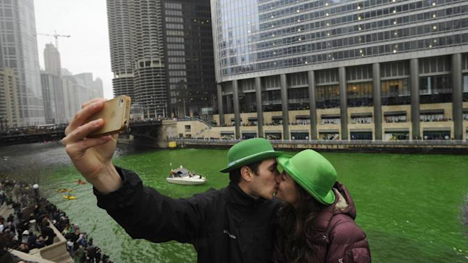 John Shepard and Gena Damento of Rochester Minn., take a photo of themselves kissing after the Chicago River was dyed green ahead of the St. Patrick's Day parade in Chicago, Saturday, March, 16, 2013.  With the holiday itself falling on a Sunday, many celebrations were scheduled instead for Saturday because of religious observances. (AP Photo/Paul Beaty)