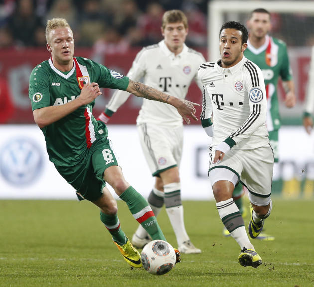 Augsburg's Kevin Vogt, left, and Bayern's Thiago Alcantara of Spain challenge for the ball during the German soccer cup third round match between FC Augsburg and FC Bayern Munich in Augsburg,