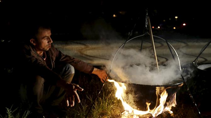 A migrant stays warm by a fire as he waits for buses bound for Austria and Germany, along the M1 highway near Budapest, Hungary