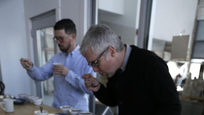 In this photo taken Thursday, Jan. 3, 2013, James Freeman, right, founder of Blue Bottle Coffee cups coffee samples, observing the tastes and aromas of brewed coffee from Uganda at his roastery in Oakland, Calif.