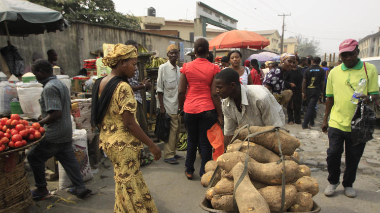 A man  sells yams at a market in Obalende  Lagos, Nigeria, Saturday, Jan. 14, 2012. Nigeria's government will meet with labor unions in a last bid to halt a paralyzing national strike that now threatens oil production in Africa's most populous nation.  (AP Photo/Sunday Alamba)