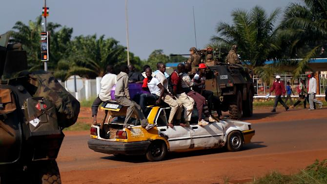 A packed taxi drives past a French checkpoint in Bangui, Central African Republic, Monday Dec. 16, 2013. Over 1600 French troops have been deployed to the country in an effort to put an end to sectarian violence. More than 600 people have been killed since Anti-Balaka launched a strike over Bangui last week before being pushed back. (AP Photo/Jerome Delay)