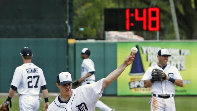 Detroit Tigers pitcher Kyle Lobstein warms up for the second inning of a spring training exhibition baseball game against the Baltimore Orioles in Lakeland, Fla., as a clock ticks down in the background, Tuesday, March 3, 2015. Digital clocks, though some officials prefer to call them timers, have been installed in ballparks throughout the Grapefruit and Cactus leagues to keep the action moving. (AP Photo/Gene J. Puskar)